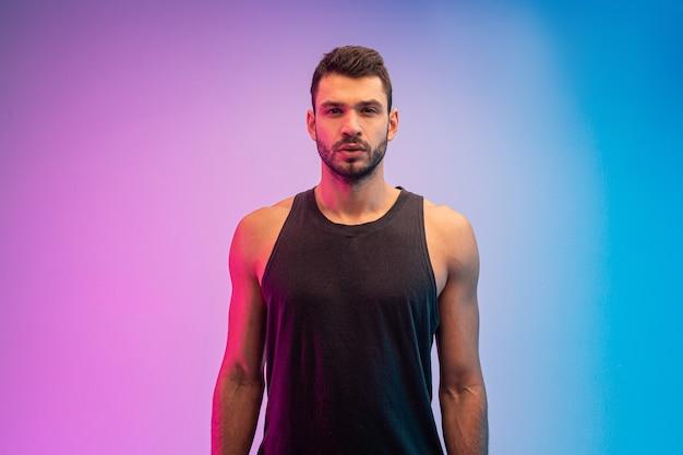 Zeker europees jonge mensenportret. knappe bebaarde man draagt tanktop en kijkt naar de camera. geïsoleerd op blauwe en roze achtergrond. studio opname. ruimte kopiëren