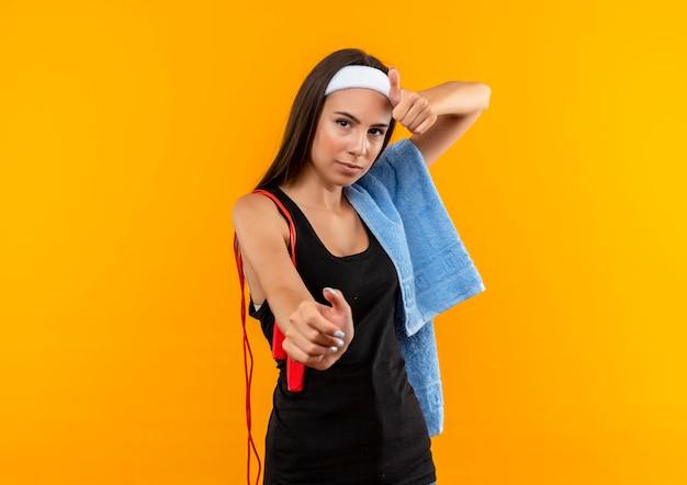 Zeker jong vrij sportief meisje die hoofdband en polsband met handdoek en touwtjespringen op haar schouders dragen die hand uitstrekken en duim op oranje muur tonen
