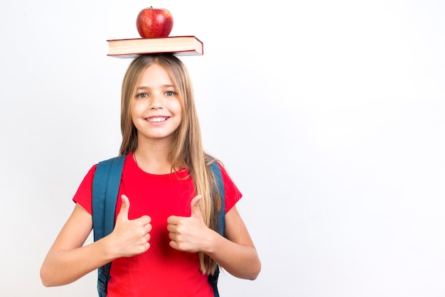 Zeker schoolmeisje in evenwicht brengend boek op hoofd