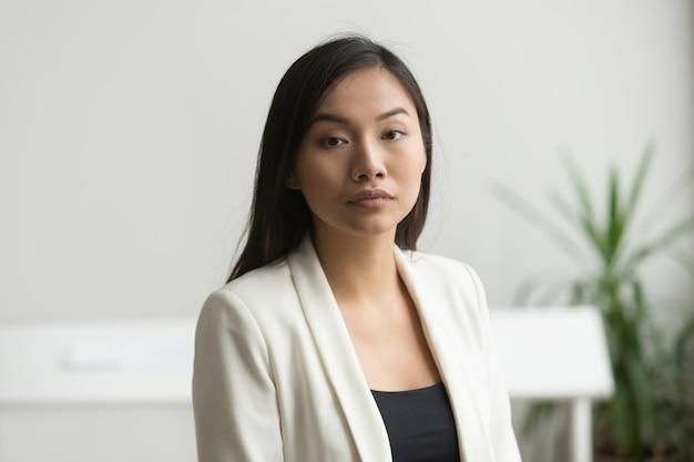 Zekere aantrekkelijke aziatische onderneemster die camera, hoofd geschoten portret bekijkt