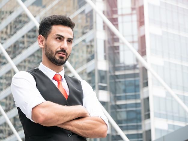 Zekere arabische zakenmanmanager die zich met gekruiste wapens openlucht op voor modern kantoor bevinden.
