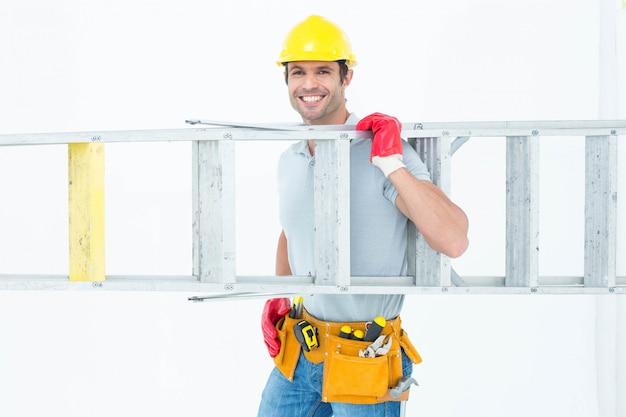 Zekere arbeider die stapladder draagt
