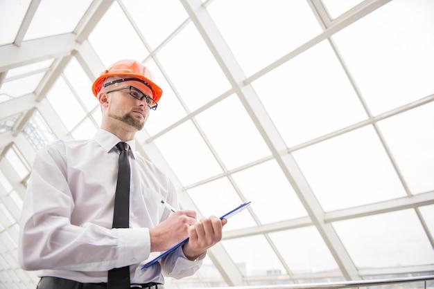 Zekere architect met helm in het kantoor.