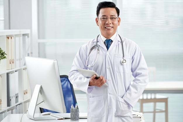 Zekere arts die camera bekijkt die tabletpc houdt
