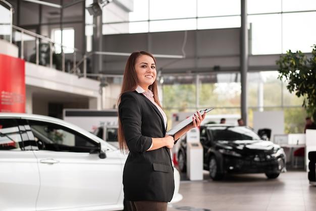 Zekere autohandelaar die een klembord houdt