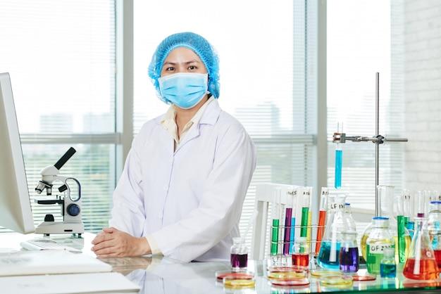 Zekere aziatische microbioloog poseren voor fotografie