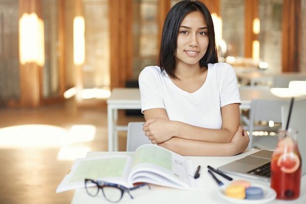 Zekere aziatische student die in bibliotheek of coworkingruimte werkt die zich klaarmaakt voor haar examens.