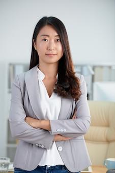 Zekere aziatische vrouw in het slimme jasje stellen in bureau met gekruiste wapens