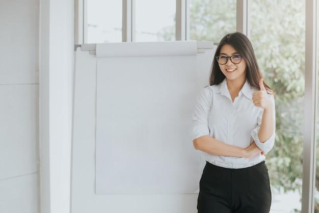 Zekere aziatische vrouw met lege flipchart