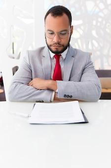Zekere bedrijfsleider die contract bestudeert