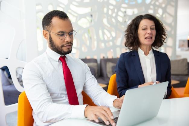 Zekere bedrijfsmensen die tijdens vergadering spreken
