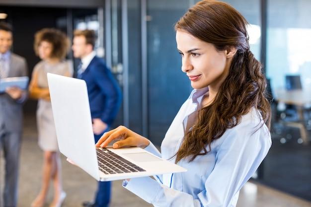 Zekere bedrijfsvrouw die laptop in bureau met haar teamblack met behulp van
