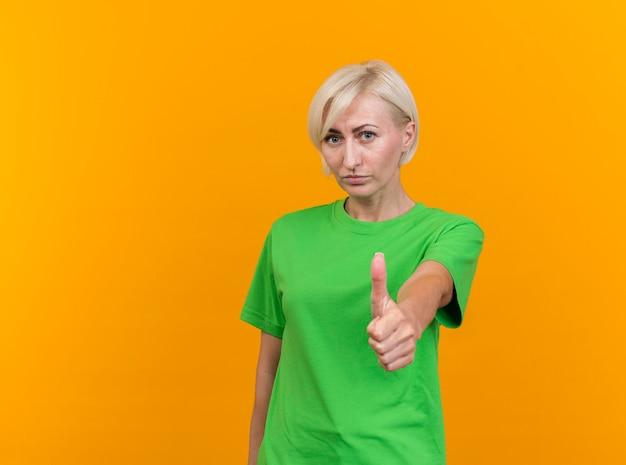 Zekere blonde slavische vrouw die van middelbare leeftijd voorzijde bekijkt die duim toont die omhoog op gele muur met exemplaarruimte wordt geïsoleerd