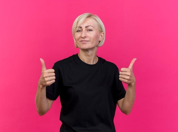 Zekere blonde vrouw die van middelbare leeftijd voorzijde bekijkt die duimen toont die omhoog op roze muur wordt geïsoleerd
