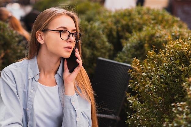 Zekere blondevrouw die op telefoon spreken