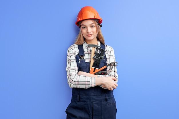 Zekere dienstvrouw die oranje helm en de blauwe moersleutel, de hamer en andere hulpmiddelen van de overallholding in handen draagt die over blauwe studioachtergrond wordt geïsoleerd