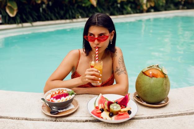 Zekere donkerbruine tan vrouw die in de rode zonnebril van kattenogen in pool met plaat van exotisch fruit tijdens tropische vakantie ontspannen. stijlvolle tatoeage.