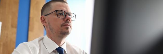 Zekere en peinzende mens die met computer op het werk werkt
