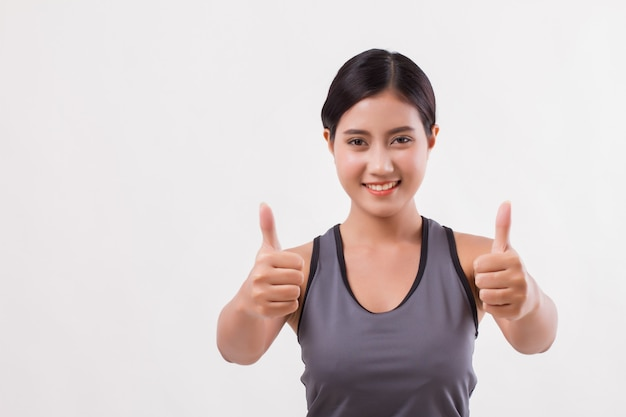 Zekere gelukkige glimlachende geschiktheidsvrouw die duim opgeeft