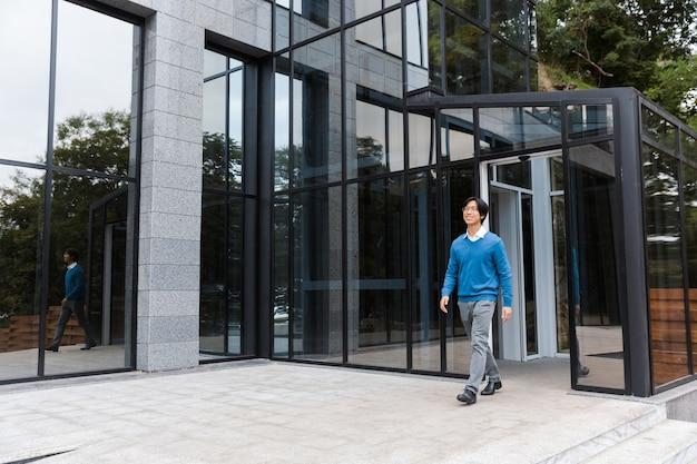 Zekere glimlachende aziatische zakenman die glasgebouw verlaat