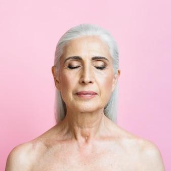 Zekere hogere vrouw met roze achtergrond