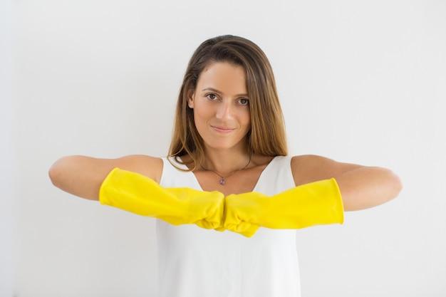 Zekere huisvrouw in rubberen handschoenen die vuisten raken