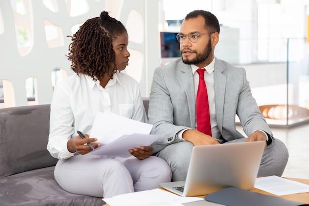 Zekere jonge bedrijfsmensen die tijdens vergadering spreken