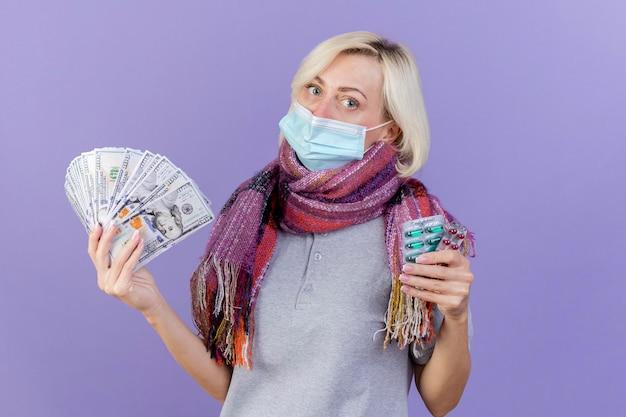 Zekere jonge blonde zieke slavische vrouw die medische masker en sjaal draagt