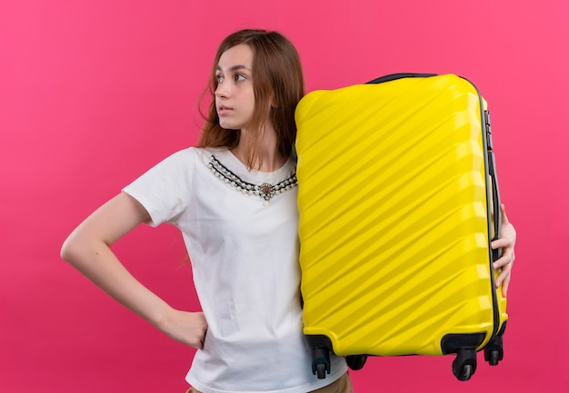 Zekere jonge de holdingskoffer die van het reizigersmeisje linkerkant op geïsoleerde roze ruimte bekijkt