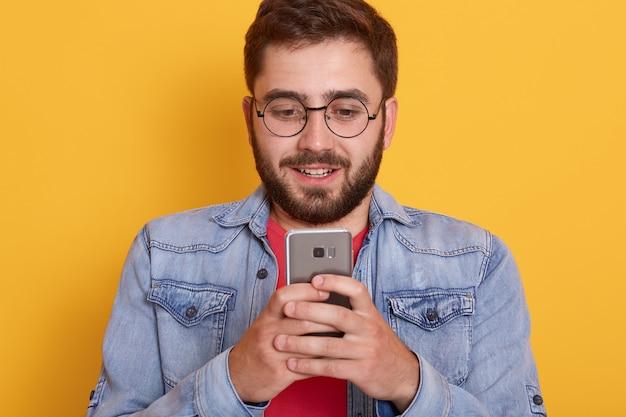 Zekere jonge gebaarde opgewekt status tegen gele muur, houdend slimme telefoon in handen, lezend bericht van zijn vriendin