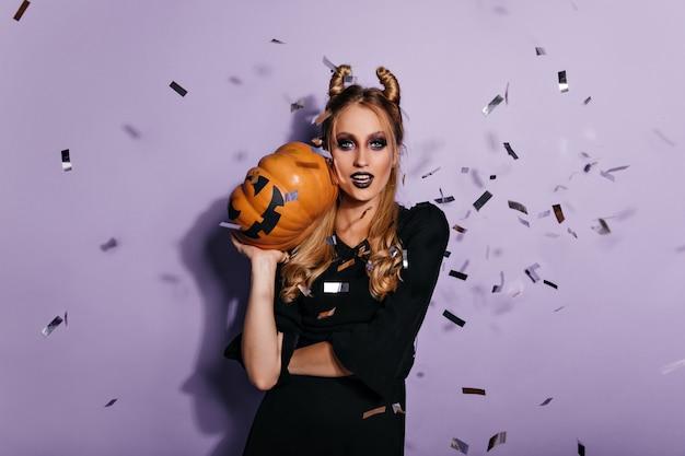 Zekere jonge heks die halloween-pompoen houdt. foto van mooie vampier meisje staande op paarse muur.
