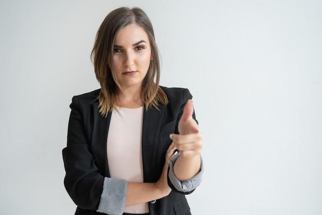 Zekere jonge kaukasische vrouw die in slim kostuum op u richt