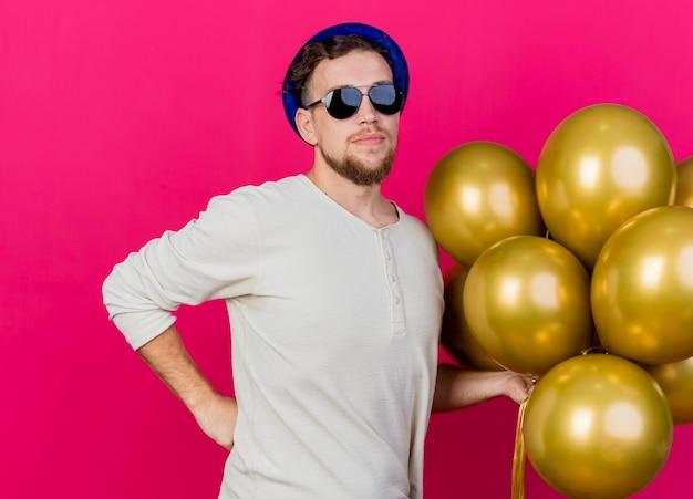 Zekere jonge knappe slavische partijkerel die partijhoed en zonnebril draagt die ballons houdt die hand op taille houdt die voorzijde bekijkt die op roze muur wordt geïsoleerd