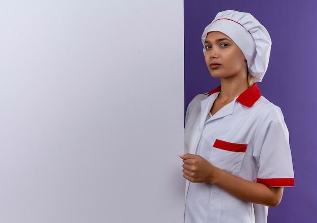 Zekere jonge kokvrouw die eenvormige chef-kok draagt die witte muur op geïsoleerde muur met exemplaarruimte houdt