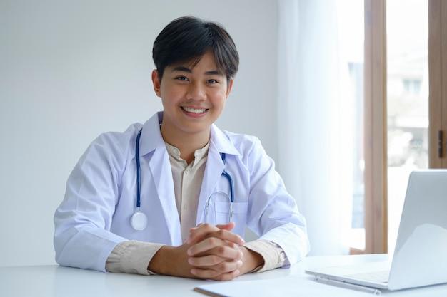 Zekere jonge mannelijke arts bij bureau.