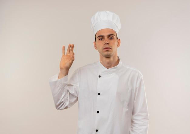 Zekere jonge mannelijke kok die eenvormige chef-kok draagt die okgebaar op geïsoleerde witte muur met exemplaarruimte toont