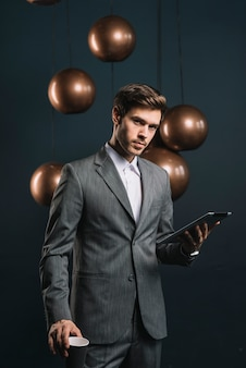 Zekere jonge mens die beschikbare kop en digitale tablet houden tegen donkere achtergrond