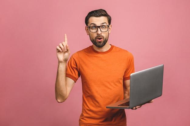 Zekere jonge mens die in vrijetijdskleding laptop houdt