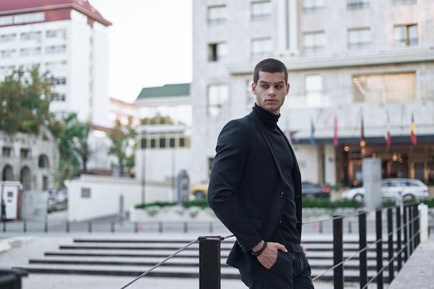 Zekere jonge mens die op een europese stadsstraat loopt
