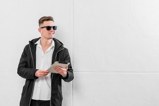 Zekere jonge mens met draadloze oortelefoon op zijn oor die digitale tablet houden die in hand weg eruit zien