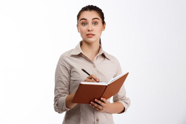 Zekere jonge mooie donkerbruine onderneemster die in notitieboekje over witte muur schrijft