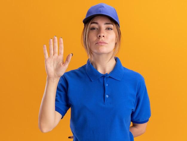 Zekere jonge mooie leveringsvrouw in uniforme tribunes met opgeheven hand die op oranje muur wordt geïsoleerd
