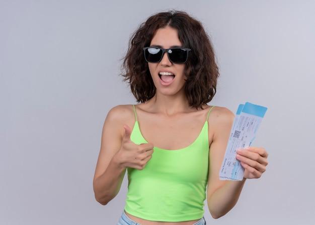 Zekere jonge mooie reizigersvrouw die zonnebril draagt en vliegtuigtickets houdt en duim op geïsoleerde witte muur met exemplaarruimte toont