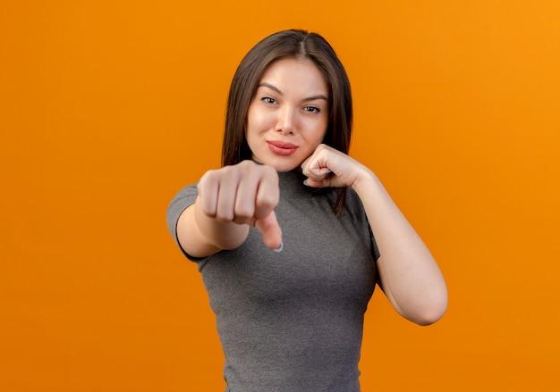 Zekere jonge mooie vrouw die boksgebaar doet bij camera die op oranje achtergrond met exemplaarruimte wordt geïsoleerd