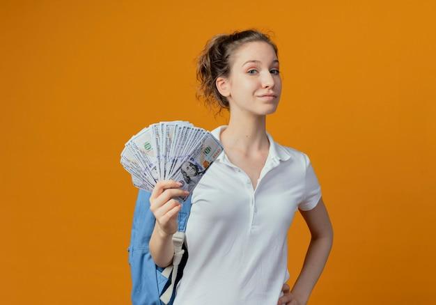 Zekere jonge mooie vrouwelijke student die achterzak draagt die geld hand op taille zet die op oranje achtergrond met exemplaarruimte wordt geïsoleerd