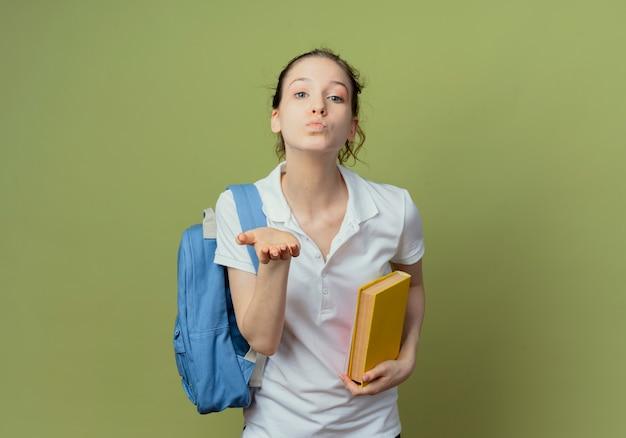 Zekere jonge mooie vrouwelijke student die het boek van de achterzakholding draagt en klapkus verzendt bij camera die op groene achtergrond met exemplaarruimte wordt geïsoleerd