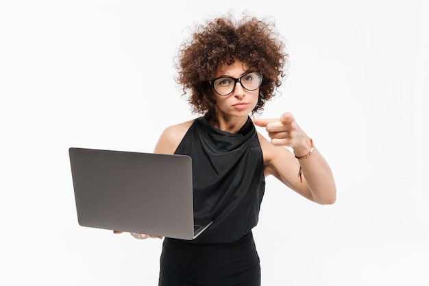 Zekere jonge onderneemster die in oogglazen laptop houdt