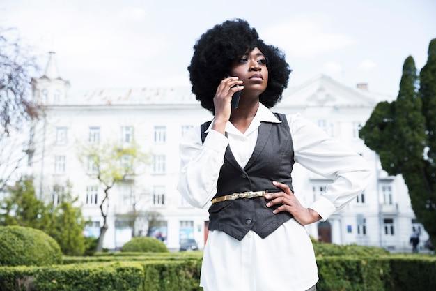 Zekere jonge onderneemster met haar handen op heup die op mobiele telefoon spreken
