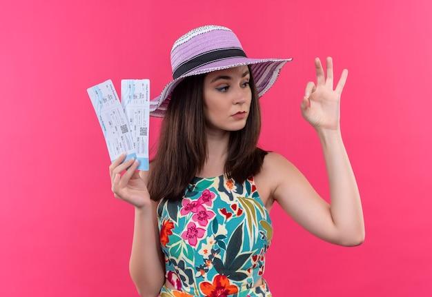 Zekere jonge reizigersvrouw die hoed draagt die ok teken doet en vliegtuigtickets houdt die zich over geïsoleerde roze muur bevinden