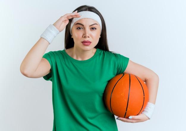 Zekere jonge sportieve vrouw die hoofdband en polsbandjes draagt die basketbalbal houden die afstand onderzoeken